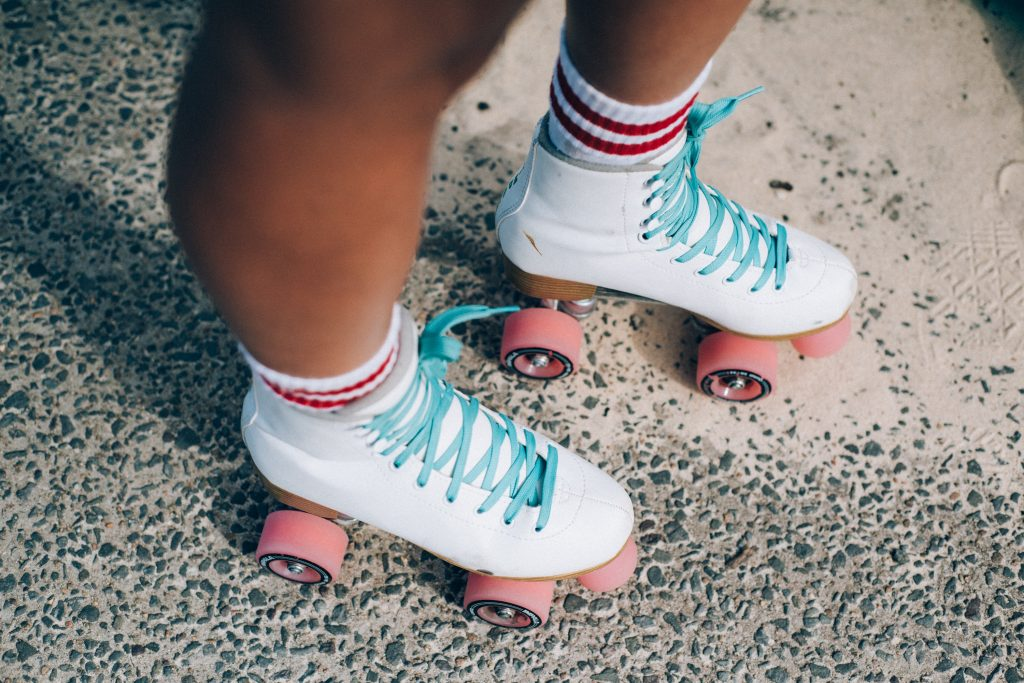 Knee down shot of girl wearing white skates with pink wheels