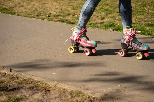 Knee down shot of person skating in colorful roller skates