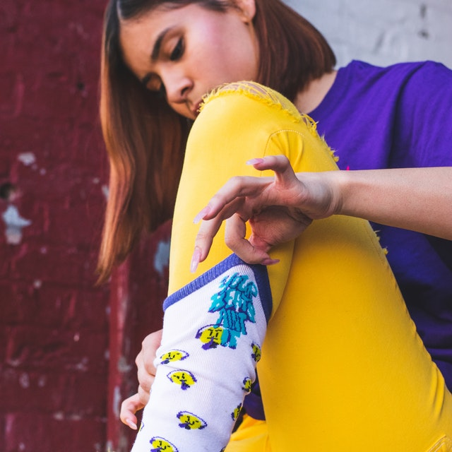 Woman in yellow pants putting on colorful socks