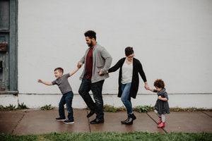 Photo of family walking while holding hands