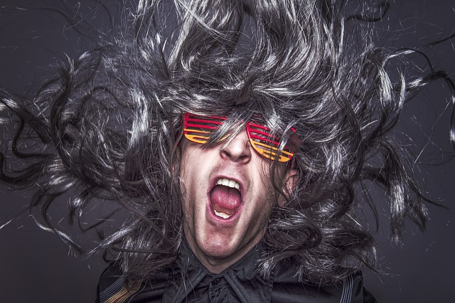 Man in wig and shutter shades costume