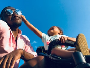 Happy dad and child interacting on sunny day
