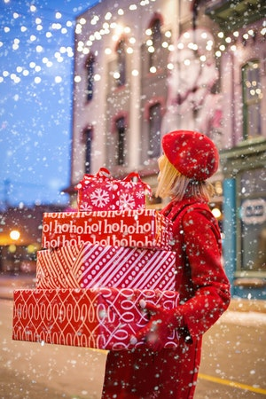 Photo of woman in red coat holding wrapped gifts in the snow