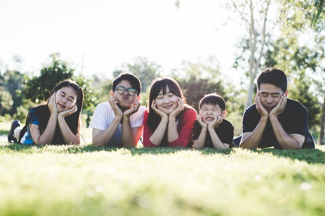 Family making silly faces on grass