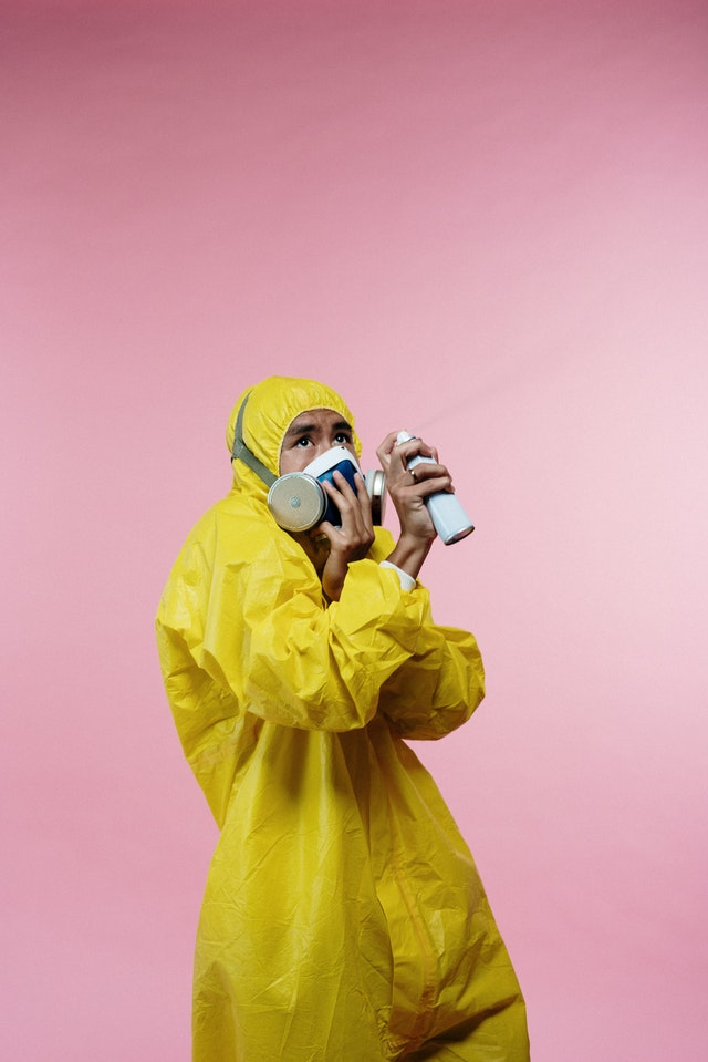 Man in yellow suit and face mask spraying disinfectant