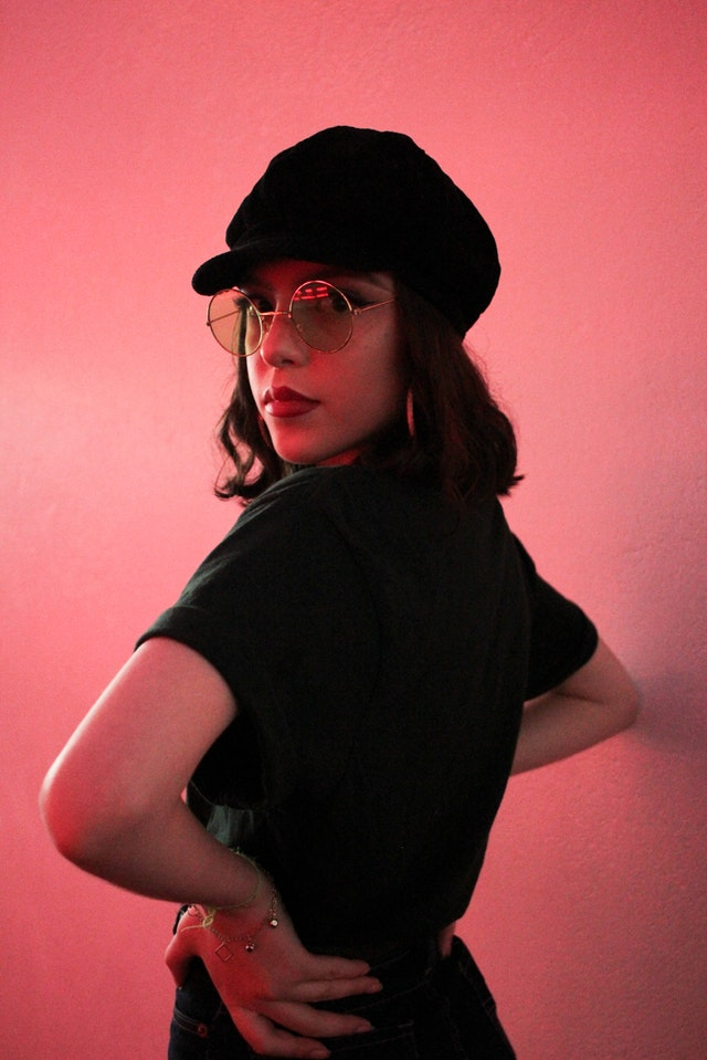 Woman in retro all black outfit with mod hat and glasses in front of pink wall