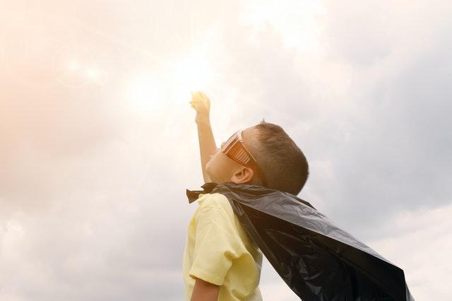 Kid with cape striking superhero pose