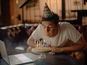 Man in party hat blowing out candles on birthday cake in front of laptop webcam
