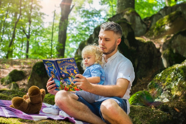 Dad reading to small child on picnic blanket