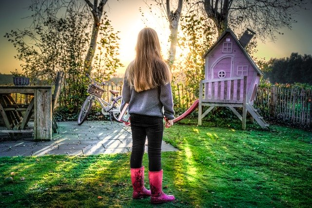 Girl standing in kid-friendly backyard at sunset