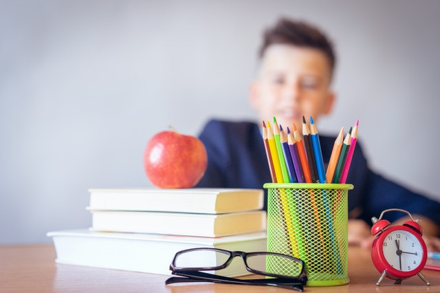 Kid sitting at desk with books and school supplies