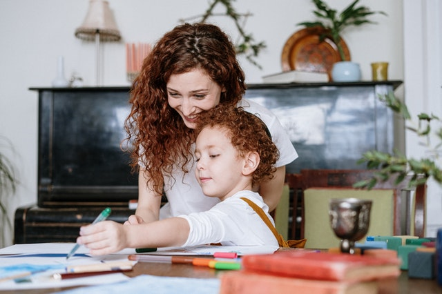 Mom helping child with homework at kitchen table