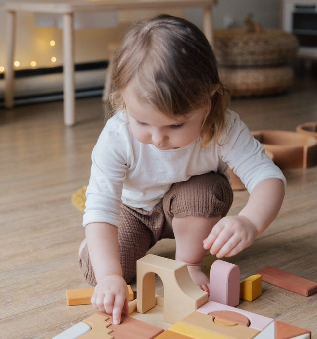 Little kid playing with wooden blocks