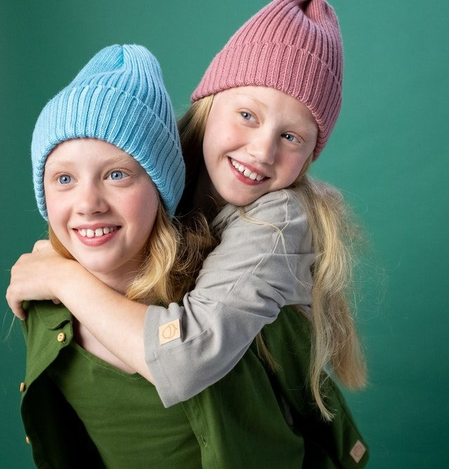 Twin girls in beanie hats giving piggyback ride