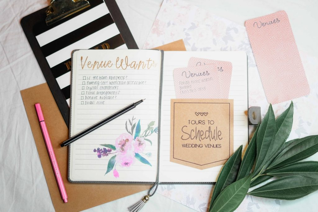 Event venue checklist in journal on desktop with trendy accessories