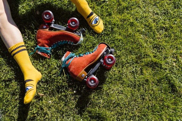 Legs in yellow socks on grass with bright orange roller skates