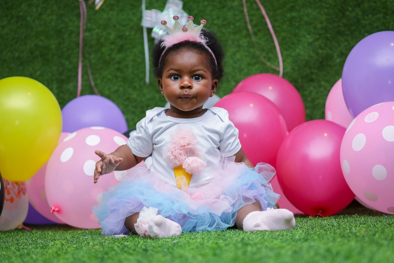 Adorable baby in birthday dress and crown sitting in front of balloons
