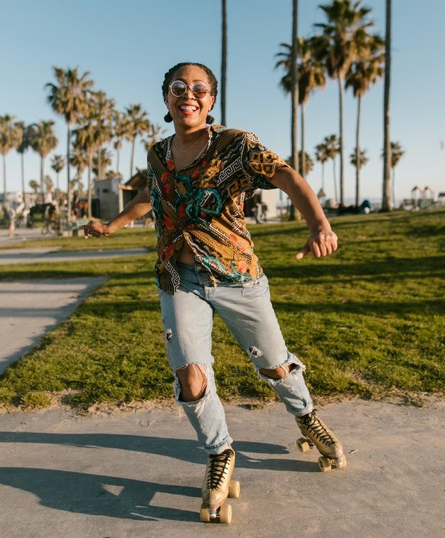 Happy woman in colorful shirt and ripped jeans skating