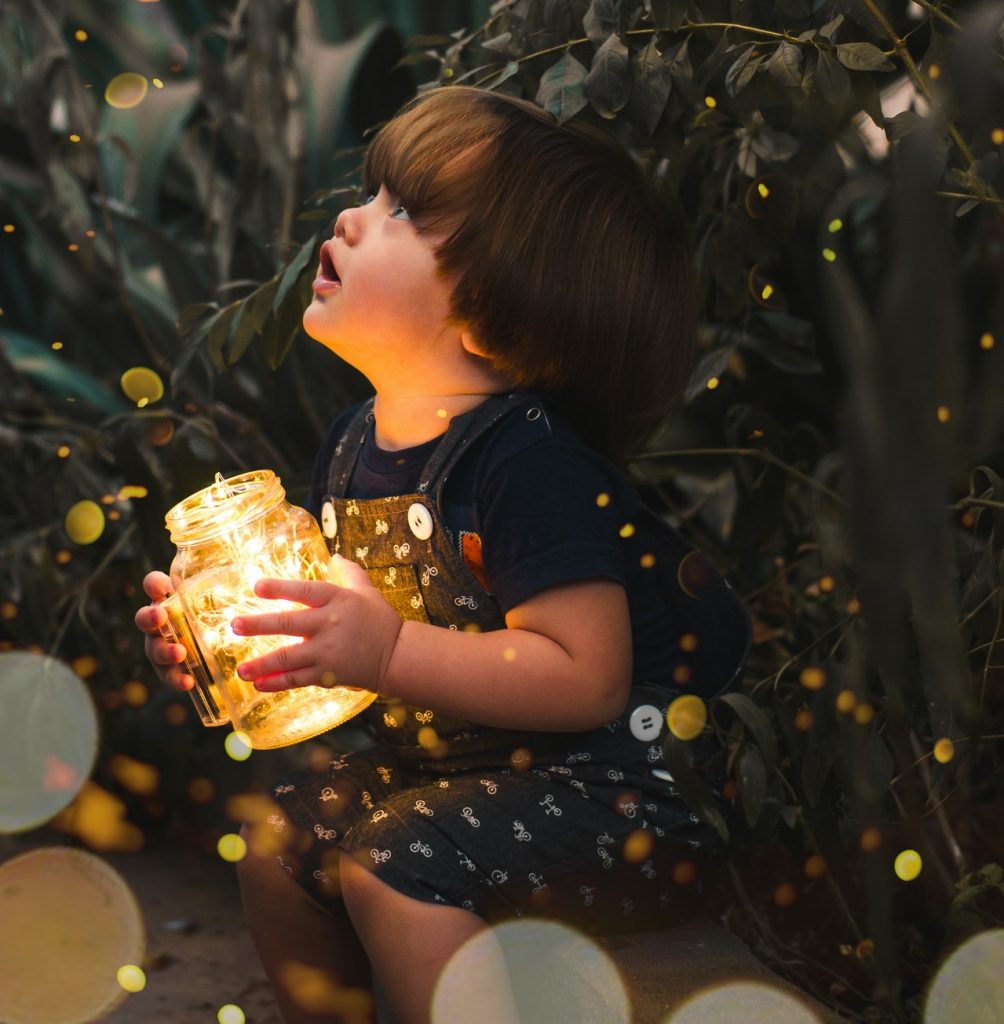 Cute kid in summer overalls holding jar of light in front of plants