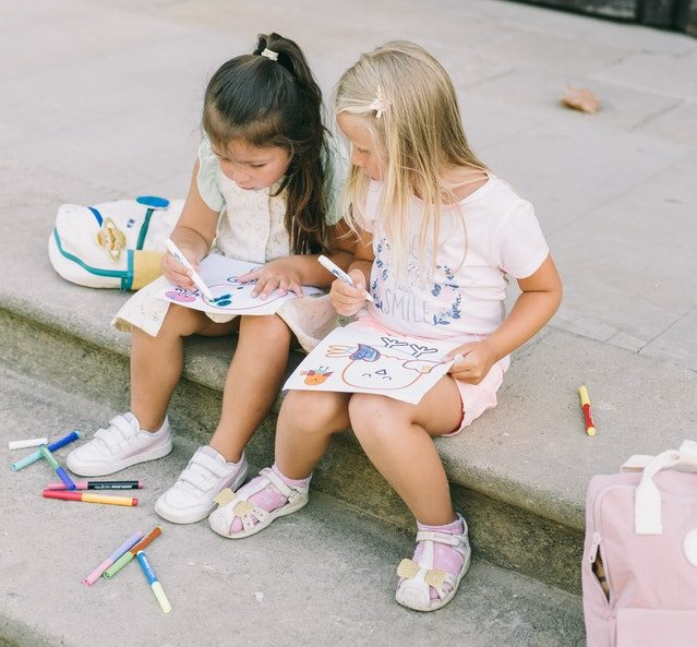 Two girls drawing outside