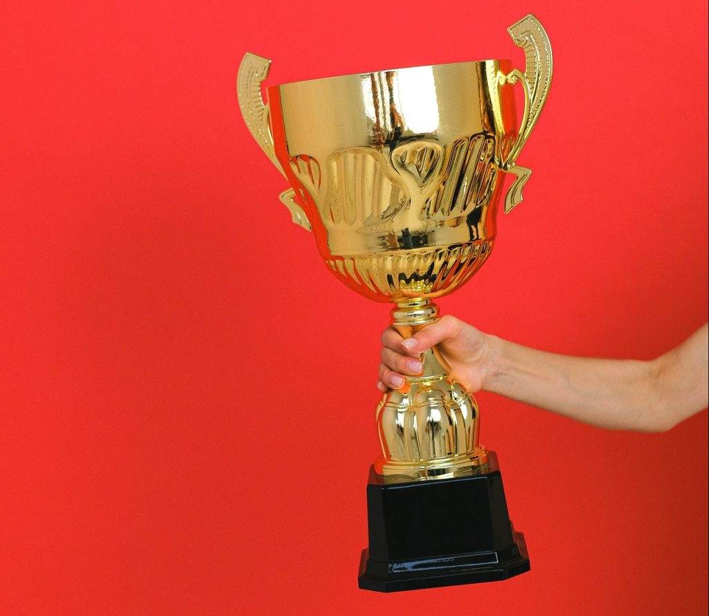 Arm holding large, gold trophy in front of red background